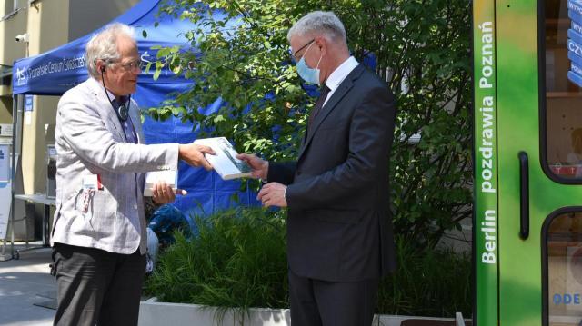Heiner Klemp bei der Buchübergabe an Stadtpräsident Jacek Jaśkowiak vor der BiblioboXX
